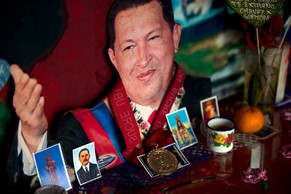 In this Friday, July 25, 2014 photo, an image of the late Venezuelan President Hugo Chavez decorated with religious images is seen inside of a small chapel at the 23 de Enero neighborhood in  Caracas, Venezuela. Nationwide commemorations took place July 28th, on what would have been the late leader's 60th birthday. (AP Photo/Fernando Llano)