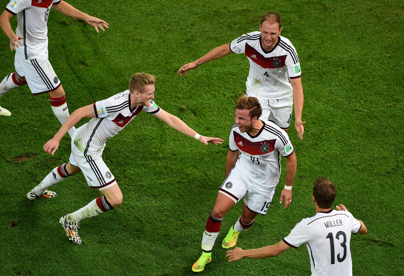 Germany's forward Mario Goetze (C) celebrates with (L/R) Germany's forward Andre Schuerrle, Germany's defender Benedikt Hoewedes and Germany's forward Thomas Mueller after scoring during extra-time in the final football match between Germany and Argentina for the FIFA World Cup at The Maracana Stadium in Rio de Janeiro on July 13, 2014. AFP PHOTO / FRANCOIS XAVIER MARIT/POOL