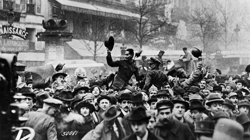 ARCHIVE --- VOR 100 JAHREN AM 11. NOVEMBER 1918 BEENDETE DER VEREINBARTE WAFFENSTILLSTAND VON COMPIEGNE DIE KAMPFHANDLUNGEN IM ERSTEN WELTKRIEG --- American soldiers join in the excitement on the Grand Boulevard in Paris as citizens celebrate the armistice on Nov. 11, 1918. The soldiers are shown riding on each others shoulders. (KEYSTONE/AP/Anonymous)