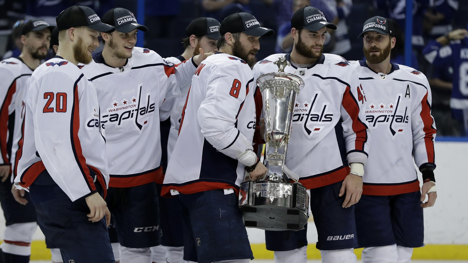Washington Capitals left wing Alex Ovechkin (8) holds the Prince of Wales trophy with teammates after the Capitals defeated the Tampa Bay Lightning 4-0 during Game 7 of the NHL Eastern Conference finals hockey playoff series Wednesday, May 23, 2018, in Tampa, Fla. (AP Photo/Chris O'Meara)