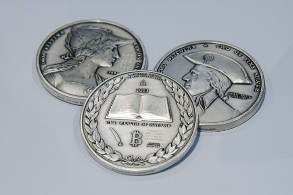 Silver coins etched with the cryptographic information for digital Bitcoins in them lie on a desk during the