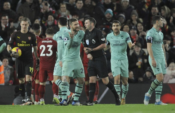Referee Michael Oliver, centre, is spoken to by Arsenal's Shkodran Mustafi, and Arsenal's Sokratis Papastathopoulos after Oliver awarded a penalty to Liverpool during the English Premier League soccer match between Liverpool and Arsenal at Anfield in Liverpool, England, Saturday, Dec. 29, 2018. (AP Photo/Rui Vieira)