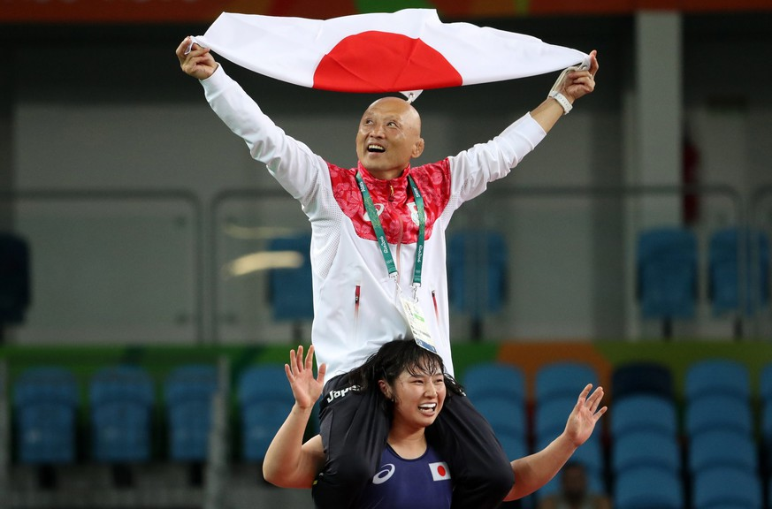 epa05494401 Sara Dosho (down) of Japan celebrates with her coach Kazuhito Sakae on her shoulders after winning the gold medal in women's Freestyle 69kg wrestling of the Rio 2016 Olympic Games Wrestling events at the Carioca Arena 2 in the Olympic Park in Rio de Janeiro, Brazil, 17 August 2016.  EPA/SERGEI ILNITSKY