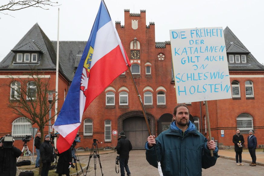 epa06629974 A protestor with a cardboard reading 'the freedom of the Catalan citizens counts in Schleswig-Holstein as well' stands in front of the  'Justizvollzugsanstalt (JVA) Neumuenster' prison, where the former Catalan leader, Carles Puigdemont, is detained in Neumuenster, Germany, 26 March 2018. German police on 25 March 2018 detained former Catalan leader Puigdemont after he crossed into Germany from Denmark. Puigdemont is sought by Spain who issued an European arrest warrant against the former leader who is living in exile in Belgium.  EPA/SRDJAN SUKI