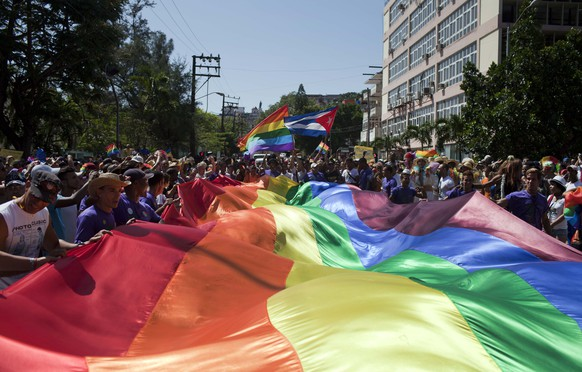 Marchers wave a giant pride banner at the start of a parade marking the upcoming International Day Against Homophobia, in Havana, Cuba, Saturday, May 10, 2014. International Day Against Homophobia is celebrated globally on May 17 commemorating the World Health Organization's declassification of homosexuality as a mental illness. (AP Photo/Franklin Reyes)