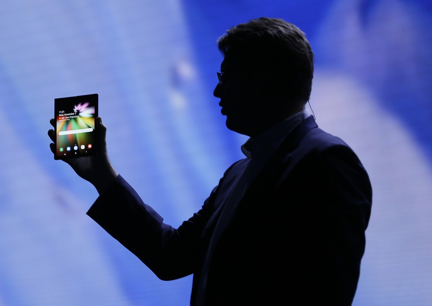 Justin Denison, SVP of Mobile Product Development, shows off the Infinity Flex Display of a folding smartphone during the keynote address of the Samsung Developer Conference, Wednesday, Nov. 7, 2018, in San Francisco. (AP Photo/Eric Risberg)
