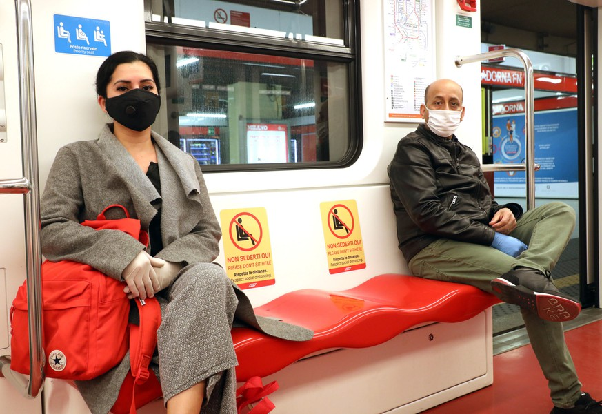 epa08386984 People wearing face masks respect social distancing measures while seated inside a subway carriage in Milan, northern Italy, 27 April 2020, during the coronavirus disease (COVID-19) pandemic.  EPA/MATTEO BAZZI