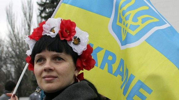 epa04662015 A local woman holds a Ukraine flag during a rally asking international community to help defend the Ukraine's territorial integrity in downtown of Mariupol, Ukraine, 14 March 2015. Ukraine has handed over a list of heavy weapons that have been withdrawn from the front line with separatist rebels, the watchdog tasked with monitoring the ceasefire in the east of the country said 13 March. The withdrawal is a key part of the peace agreement signed between Ukraine, Russia, the separatists and the OSCE in Minsk one month ago. The OSCE has complained that it cannot verify the withdrawal as long as both sides do not submit detailed information about the weapons.  EPA/IRINA GORBASYOVA  EPA/IRINA GORBASYOVA