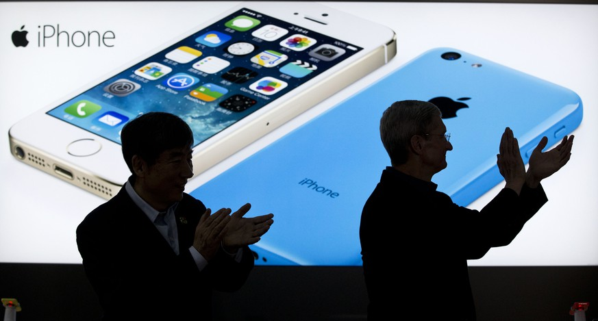 Apple CEO Tim Cook, right, and China Mobile's chairman Xi Guohua are silhouetted against a screen showing iPhone products as they applaud during a promotional event that marks the opening day of sales of China Mobile's 4G iPhone 5s and iPhone 5c at a shop of the world's largest mobile phone operator in Beijing, China, Friday, Jan. 17, 2014. (AP Photo/Alexander F. Yuan)