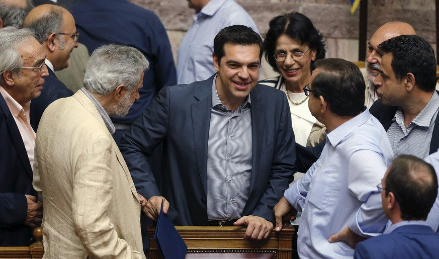 Greek Prime Minister Alexis Tsipras (C) is congratulated by lawmakers after a voting session at the Parliament in Athens, Greece, July 11, 2015. The Greek parliament voted overwhelmingly on Saturday in favour of authorizing the left-wing government of Tsipras to negotiate with international creditors on the basis of a reform programme unveiled this week.REUTERS/Christian Hartmann
