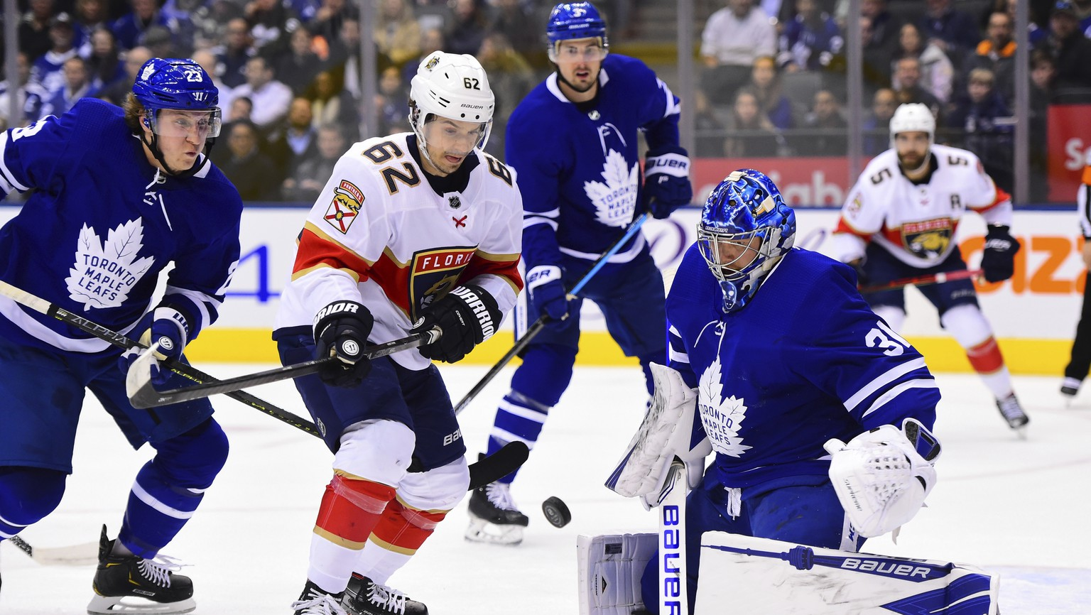 Florida Panthers center Denis Malgin (62) moves in on Toronto Maple Leafs goaltender Frederik Andersen (31) as Maple Leafs Travis Dermott (23) defends during the first period of an NHL hockey game, Monday, Feb. 3, 2020 in Toronto. (Frank Gunn/The Canadian Press via AP)