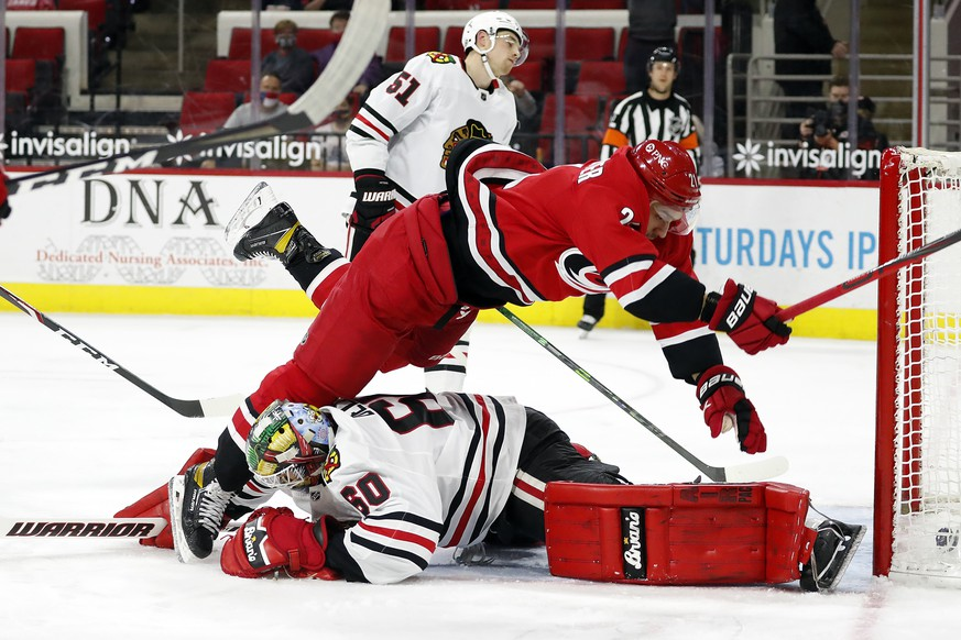 Carolina Hurricanes' Nino Niederreiter (21) collides with Chicago Blackhawks goaltender Collin Delia (60) after scoring a goal during the second period of an NHL hockey game in Raleigh, N.C., Tuesday, May 4, 2021. (AP Photo/Karl B DeBlaker)