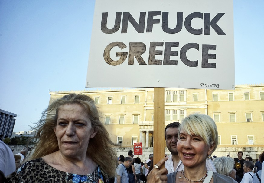 ATHENS, GREECE - JUNE 17: (EDITORS NOTE: IMAGE CONTAINS PROFANITY) Protesters during a pro-government rally calling on Greece's European and International Monetary creditors to soften their stance in the cash-for-reforms talks on June 17, 2015 in Athens, Greece. The European Commission has said that Greece and its international creditors need to come to an agreement within the next 2 weeks to avoid a possible default, after weekend talks collapsed. (Photo by Milos Bicanski/Getty Images)