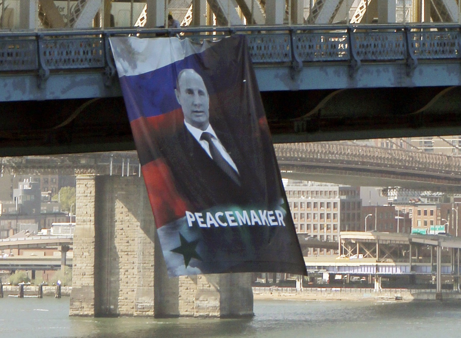 In this photo provided by Gothamist.com, a banner bearing an image of Russian President Vladimir Putin showing him with a Russian and Syrian flag as backdrop and labeling him a