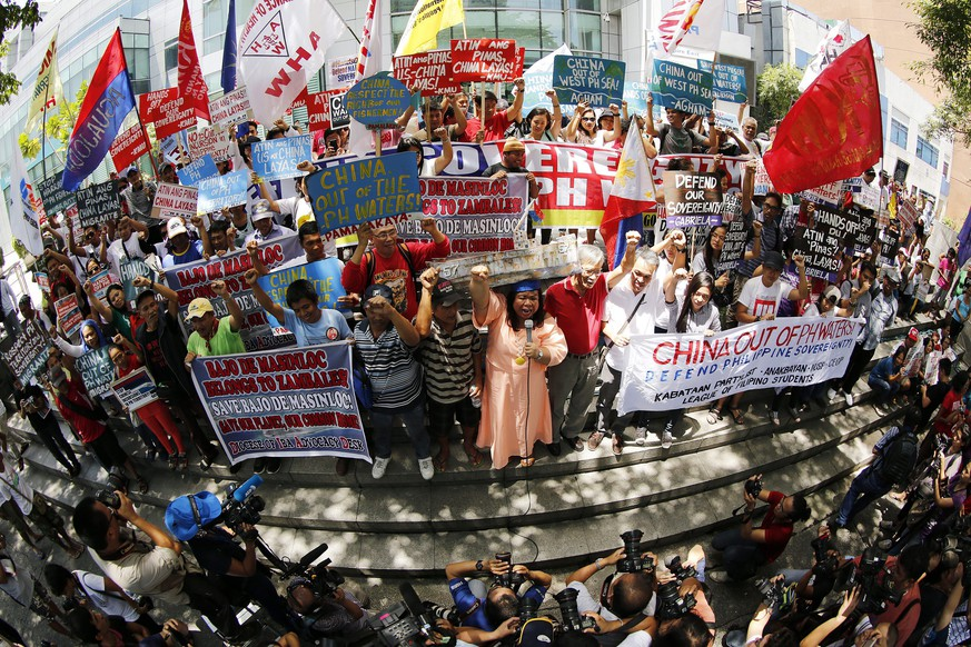 epa05421272 A picture taken with fisheye lens shows Filipino protestors hold placards as they protest against China's territorial claims over the disputed Spratlys group of islands outside the Chinese consular office in Makati, south of Manila, Philippines, 12 July 2016. According to the leader of the demonstrators, the mass action made ahead of the expected ruling of the International Tribunal of the Permanent Court of Arbitration on a case the Philippines brought in 2013 against China's claims in the South China Sea.  EPA/FRANCIS R. MALASIG