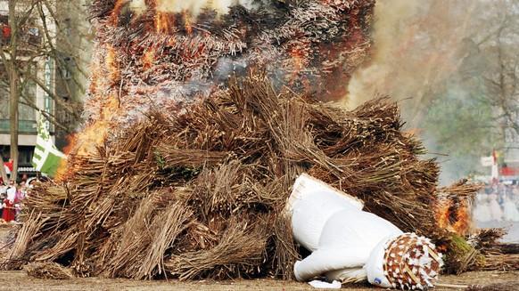 Am traditionellen Sechselaeuten vom 19. April 1993 in Zuerich will der Boeoegg nicht so abrennen wie erwartet, sondern stuerzt zur Seite und entgeht so den Flammen. Schliesslich muss der Kopf des Boeoeggs eigenhaendig ins Feuer geworfen werden. (KEYSTONE/Str)