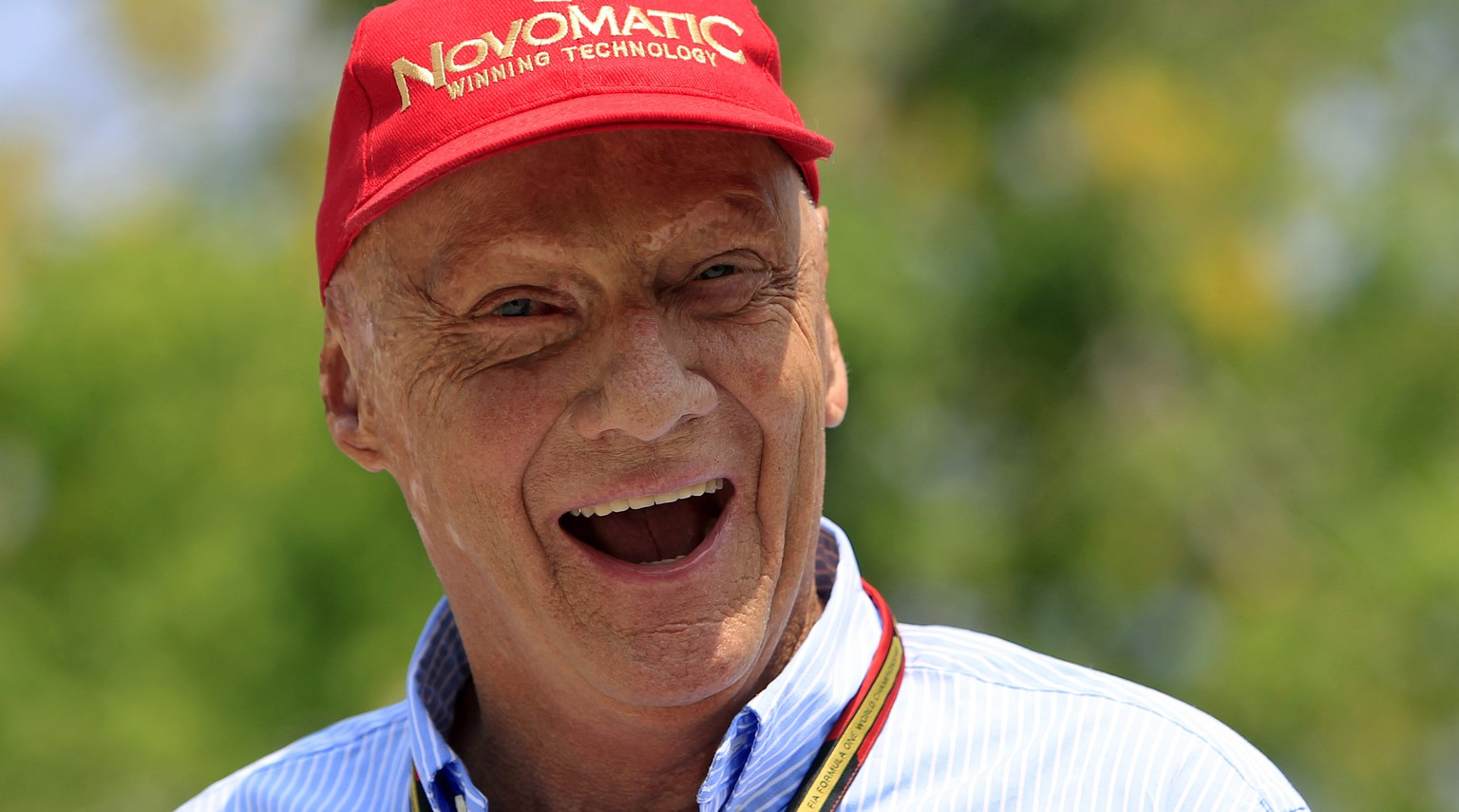 Former Formula One driver Niki Lauda of Austria laughs as he arrives at the paddock before the Malaysian Formula One Grand Prix at Sepang International Circuit in Sepang, Malaysia, Sunday, March 30, 2014. (AP Photo/Lai Seng Sin)
