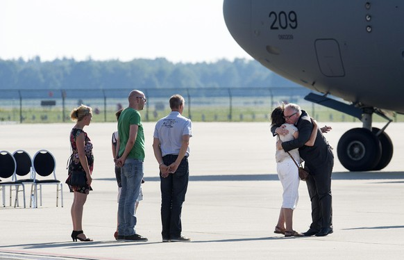 Dutch Minister of Foreign Affairs, Frans Timmermans (R), comforts a relative of a victim after the arrival of the plane carrying the bodies of the victims killed in the Malaysia Airlines Flight MH17 plane disaster, taxis into Eindhoven Airport July 23, 2014. A Dutch air force transport plane carrying the first 16 coffins with the remains of victims of the downed Malaysian airliner landed at Eindhoven airport on Wednesday from an airport in the eastern Ukrainian city of Kharkiv. REUTERS/Toussaint Kluiters/United Photos (NETHERLANDS - Tags: TRANSPORT DISASTER POLITICS)