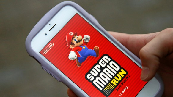 """Takuya Nishya shows Nintendo's """"Super Mario Run"""" game on his smartphone by the request of a photographer in Tokyo, Japan, December 20, 2016. Picture taken on December 20, 2016.   REUTERS/Kim Kyung-Hoon"""