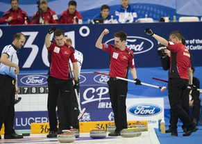 Switzerland's Dominik Marki, second left, Peter de Cruz, second right, and Valentin Tanner, right, celebrate after they scored a point against Scotland at the World Men's Curling Championship at the Capital Gymnasium in Beijing, China Monday, March 31, 2014. (AP Photo/Andy Wong)