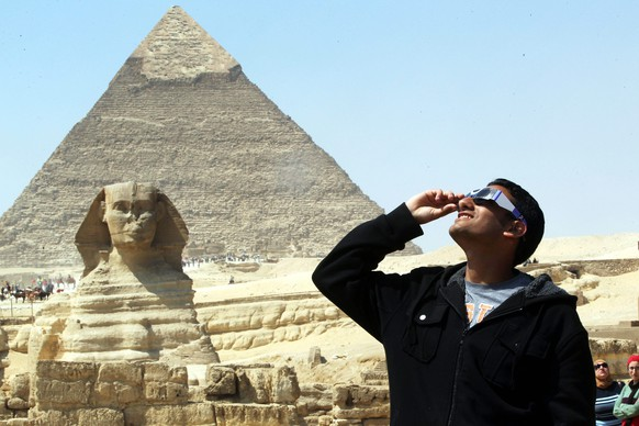 epa04671305 An Egyptian wearing special glasses watches a partial solar eclipse, from near the Sphinx at the Giza pyramids on the outskirts of Cairo, Egypt, 20 March 2015. The partial eclipse was visible across Europe and parts of Asia and Africa, while sky-gazers in the Arctic were treated to a perfect view of a total solar eclipse as the moon completely blocked out the sun in a clear sky.  EPA/KHALED ELFIQI