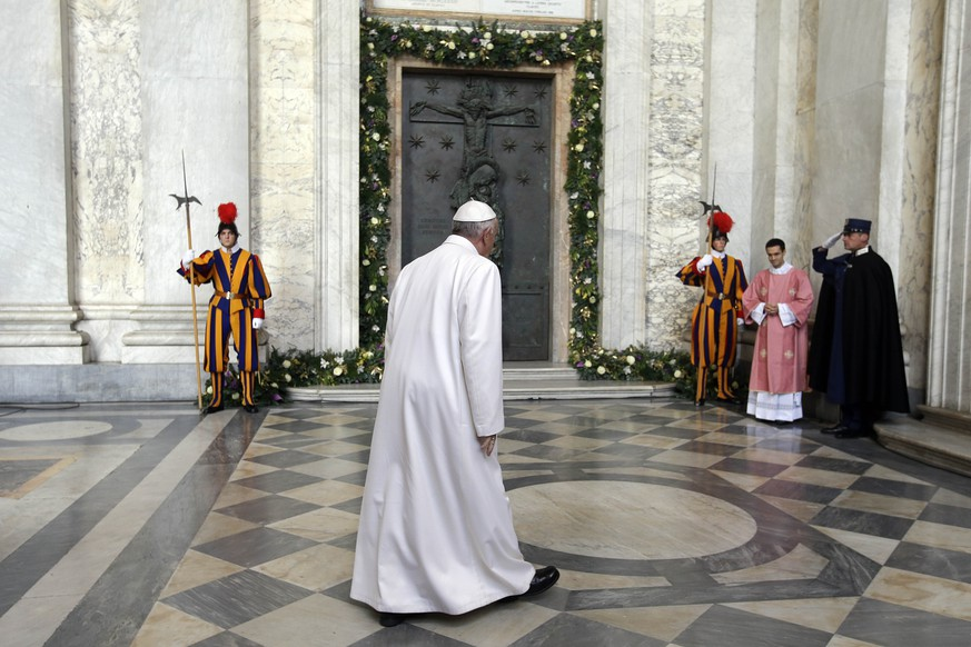Pope Francis walks past the Holy Door of St. John in Lateran Basilica prior to the start of its opening ceremony in Rome, Sunday, Dec. 13, 2015. (AP Photo/Gregorio Borgia)