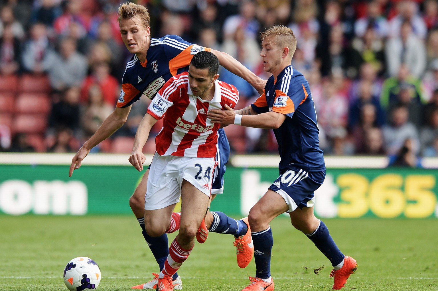 STOKE ON TRENT, ENGLAND - MAY 03:  Oussama Assaidi (C) of Stoke City is challenged by Dan Burn (L) and Lewis Holtby (R) of Fulham during the Barclays Premier League match between Stoke City and Fulham at the Britannia Stadium on May 3, 2014 in Stoke on Trent, England.  (Photo by Gareth Copley/Getty Images)