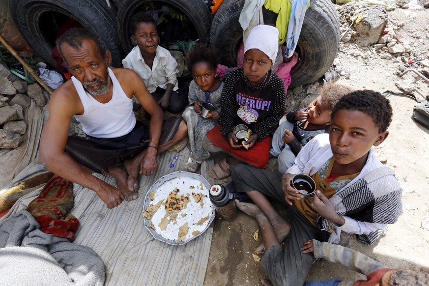 epa07467554 Displaced Yemenis share a meal inside a temporary shelter at a camp for Internally Displaced Persons (IDPs) on the outskirts of Sana'a, Yemen, 27 March 2019. According to reports, the World Food Programme (WFP) has warned of famine-like conditions unfolding in war-torn Yemen as nearly 20 million people, some 70 percent of the population, are food insecure, including about 10 million on the brink of famine, due to four years of escalating conflict in the poorest Arab country.  EPA/YAHYA ARHAB