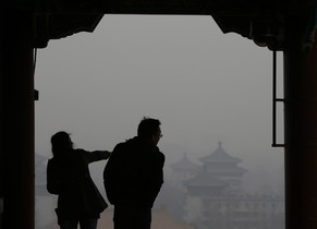 Visitors are silhouetted against thick smog on the top of Jingshan Park near the Forbidden City in Beijing February 24, 2014.  In Beijing, which has been shrouded in smoky, white smog for a week, authorities raised the air pollution alert system to
