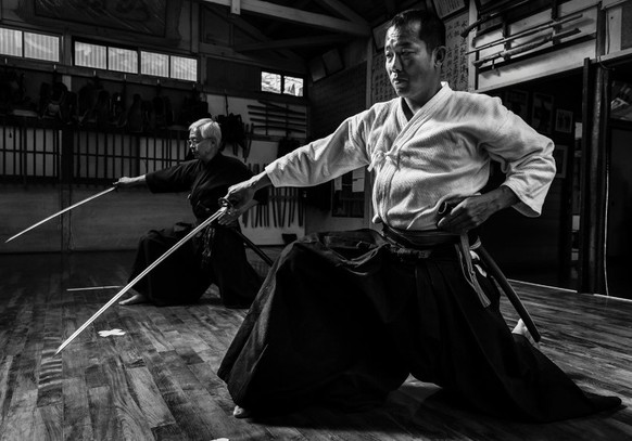 SHIMIZU KU, SHIZUOKA CITY, TOKYO, 16 OCTOBER 2014: Advanced students practise sword skills in the dojo of Master Sensei Yoshimitsu (Kagehiro) Katsuse, a master of all 18 of the Samurai arts. This dojo dates back to the 16th century and is one of very few pure Samurai dojos that survive today. Series Name: The last SamuraiSeries Description: This series depicts the state of the Samurai today, as seen through the 4 most revered remaining masters and their students.