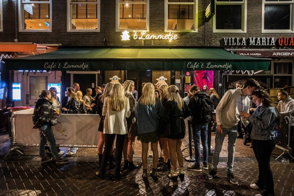 epa09302179 Cafe visitors hang out near a pub after 10pm in Amsterdam, The Netherlands, late 25 June 2021. Starting from 26 June 2021, a number of coronavirus restrictions in the country will be lifted. Face mask requirement will drop in most situations except where the social distancing of at least 1.5 meter cannot be guaranteed, such as in public transport, stations, in airports, on airplanes and other forms of passenger transport and in secondary schools. The ban on the sale of alcohol or drinking alcohol in public spaces after 22.00 will be also lifted. Despite the fact that relaxations took effect on 26 June at midnight, Justice Minister Ferg Grapperhaus did not mind if mayors dealt with it mildly and decided not to enforce the rules on 25 June evening.  EPA/PAUL BERGEN