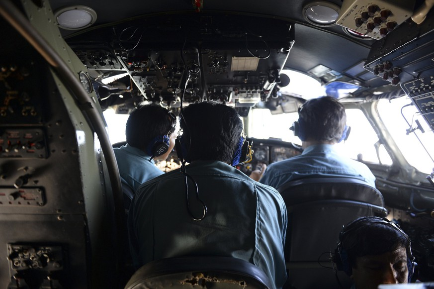 Vietnamese Air Force officers sit in the cockpit of a search and rescue aircraft as they fly over the search area for a missing Malaysia Airlines plane, 250 km from Vietnam and 190 km from Malaysia, March 9, 2014. Malaysia Airlines said it was