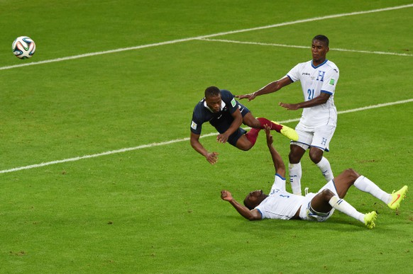 France's defender Patrice Evra (L) vies for the ball with Honduras' defender Maynor Figueroa (down) and defender Brayan Beckeles, during a Group E football match between France and Honduras at the Beira-Rio Stadium in Porto Alegre during the 2014 FIFA World Cup on June 15, 2014.  AFP PHOTO / LUIS ACOSTA