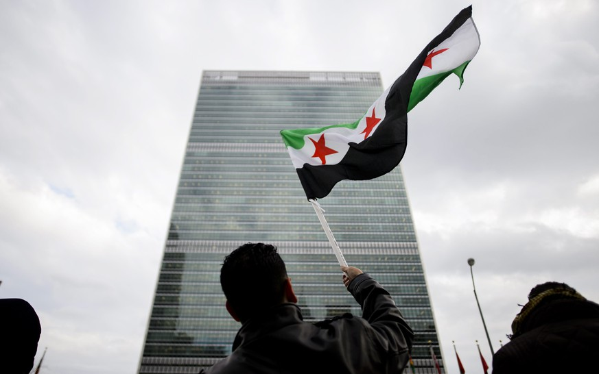epa05074606 Hamid Imam, a Syrian who lives in Patterson, New Jersey, waves the Syrian revolutionary flag while gather with other protestors in front of United Nations headquarters as foreign ministers from major world powers gather to negotiate an proposed end to the Syrian civil war, in New York, New York, USA, 18 December 2015. Major world powers are convening at the United Nations Security Council in the hopes of establishing a road map for peace in the region.  EPA/JUSTIN LANE