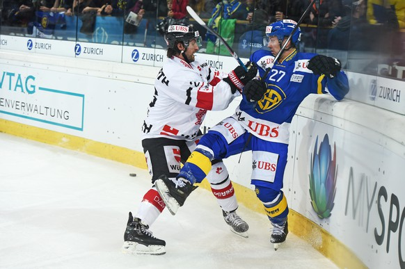 Davos Per Ledin, right, fights for the puck against Canadas Shaun Heshka, left, during the game between Switzerlands HC Davos and Team Canada at the 90th Spengler Cup ice hockey tournament in Davos, Switzerland, Tuesday, December 27, 2016. (KEYSTONE/Melanie Duchene)