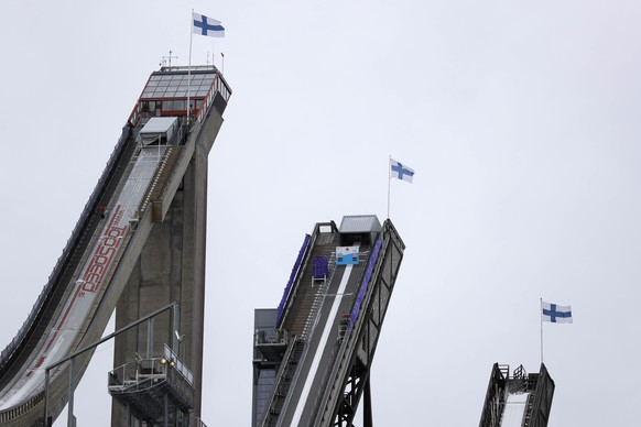 Finnish flags wave at the towers of the ski jumping Hills prior to the 2017 Nordic Skiing World Championships in Lahti, Finland, Wednesday, Feb. 22, 2017. Women's and men's training was canceled due to bad weather. (AP Photo/Matthias Schrader)