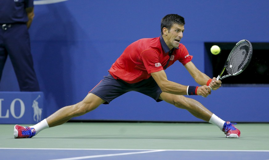Novak Djokovic of Serbia reaches to return a shot to Roberto Bautista Agut of Spain during their fourth round match at the U.S. Open tennis tournament in New York, September 6, 2015. REUTERS/Eduardo Munoz