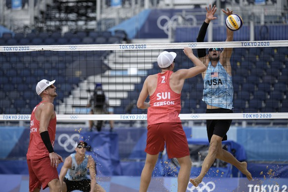 Jacob Gibb, right, of the shot of of the United States, goes up for the block of Mirco Gerson, of Switzerland, while teammates Adrian Heidrich, second from left, and Tri Bourne, second from left, look on during a men's beach volleyball match against at the 2020 Summer Olympics, Wednesday, July 28, 2021, in Tokyo, Japan. (AP Photo/Felipe Dana) Jacob Gibb,Mirco Gerson,Tri Bourne,Adrian Heidrich