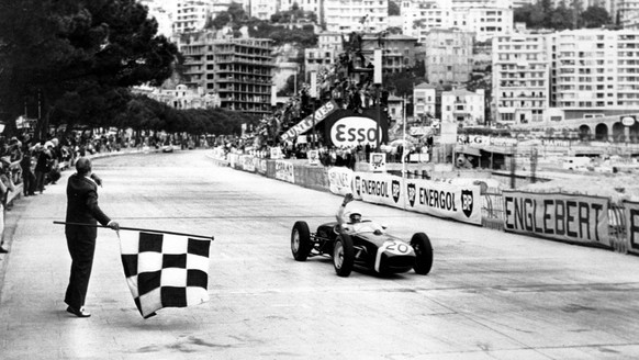 Stirling Moss of Britain raises his hand in victory after passing the finish line in first place at the Monaco Grand Prix Automobile race on May 14, 1961.  (KEYSTONE/AP Photo/Str) ===  ===