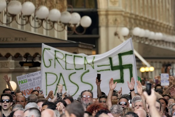 """People stage a protest against the """"green pass"""" in Milan, Italy, Saturday, July 24, 2021. Italy's government approved a decree ordering the use of the so-called """"green"""" passes starting on Aug. 6. To be eligible for a pass, individuals must prove they have received at least one vaccine dose in the last nine months, recovered from COVID-19 in the last six months or tested negative in the previous 48 hours. The passes will be needed to dine at tables inside restaurants or cafes, to attend sports events, town fairs and conferences, and to enter casinos, bingo parlors and pools, among other activities. according to officials. (AP Photo/Ricardo De Luca)"""