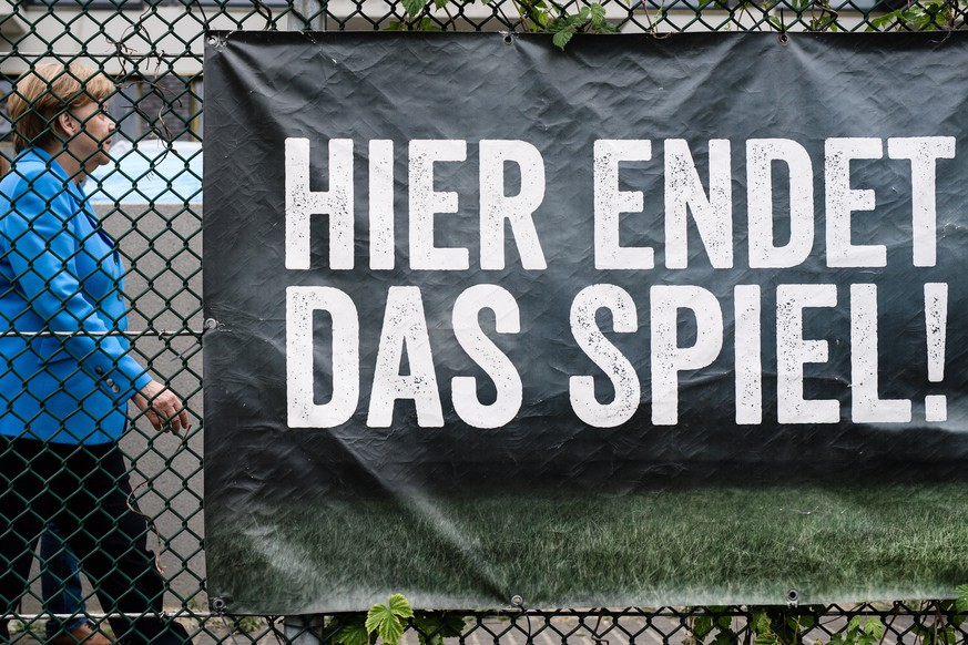 epa06804238 German Chancellor Angela Merkel passes-by a poster reading: 'Here the game ends!', after a visit to the sports club 'SV Rot-Weiss Viktoria Mitte 08', in Berlin, Germany, 13 June 2018. German Chancellor Angela Merkel informed herself on a project for the integration of young girls through sports.  EPA/CLEMENS BILAN