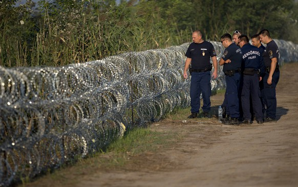 Hungarian police inspect a barbed wire fence on the border with Serbia, in Roszke, Hungary, Saturday, Aug. 29, 2015. Migrants fearful of death at sea in overcrowded and flimsy boats have increasingly turned to using a land route to Europe through the Western Balkans. (AP Photo/Darko Bandic)