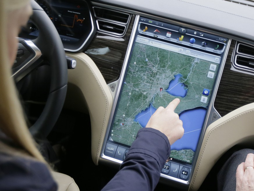 In a photo from Tuesday, April 7, 2015 in Detroit, Alexis Georgeson of Tesla Motors, shows off the navigation screen of the new Tesla Model S 70D during a test drive. Electric car maker Tesla Motors is seeking mainstream luxury buyers by adding all-wheel-drive and more range and power to the base version of its only model. Starting Wednesday, Tesla will stop selling the old base Model S called the 60 and replace it with the 70-D. The new car can go 240 miles per charge and from zero to 60 in 5.2 seconds. (AP Photo/Carlos Osorio)