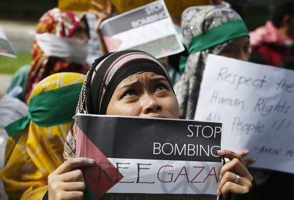 A Filipino Muslim woman holds a placard as she looks up at the building housing the Israel embassy, during a rally held by the Anak Mindanao (Children of Mindanao) Party List group in Taguig, Metro Manila, July 15, 2014.  The rally called on the United Nations to help resolve the ongoing conflict between Israel and Palestinian militants in Gaza, and for both sides to agree to an immediate ceasefire, the Anak Mindanao party said in a statement.      REUTERS/Erik De Castro (PHILIPPINES - Tags: POLITICS CIVIL UNREST CONFLICT RELIGION)