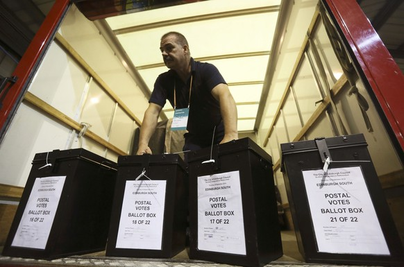 A man carries ballot boxes at a counting centre in Edinburgh, Scotland, September 18, 2014. Scotland voted on Thursday on whether to stay within the United Kingdom or end the 307-year-old union with England and become an independent nation in a finely balanced referendum with far-reaching consequences.    REUTERS/Paul Hackett (BRITAIN  - Tags: POLITICS ELECTIONS)