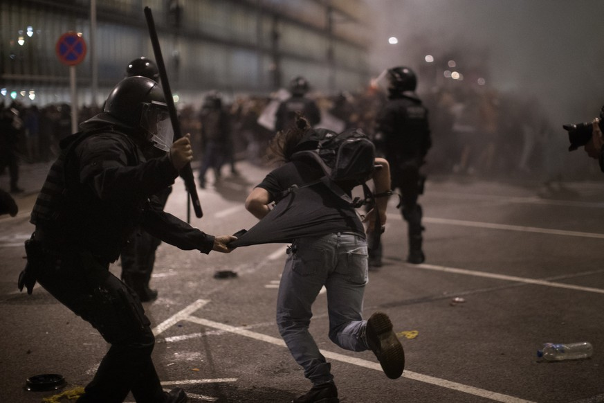 Demonstrators run away from Police officers outside El Prat airport in Barcelona, Spain, Monday, Oct. 14, 2019. Riot police have charged at protesters outside Barcelona's airport after the Supreme Court sentenced 12 prominent Catalan separatists to lengthy prison terms for their roles in a 2017 push for the wealthy Spanish region's independence. (AP Photo/Emilio Morenatti)
