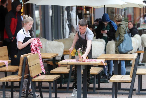 epa09201565 Waiters prepare tables of an outdoor restaurant after its reopening in Zakopane, southern Poland, 15 May 2021. Poland is easing its coronavirus restrictions after a significant decline in new coronavirus cases, allowing from 15 May to reopen open-air gardens at restaurants and gastronomic premises for customers and also face masks are no longer required outdoors.  EPA/GRZEGORZ MOMOT POLAND OUT