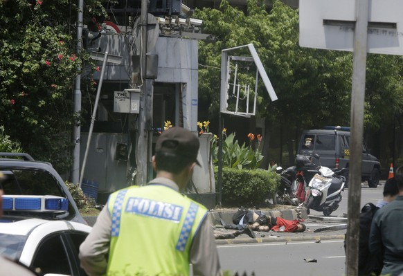 EDS NOTE: GRAPHIC CONTENT - Bodies are seen as a police officer walks near a police post damaged by an explosion in Jakarta, Indonesia, Thursday, Jan. 14, 2016. Suicide bombers exploded themselves in downtown Jakarta on Thursday while gunmen attacked a police post nearby, a witness told The Associated Press. Local television reported more explosions in other parts of the city. (AP Photo/Dita Alangkara)