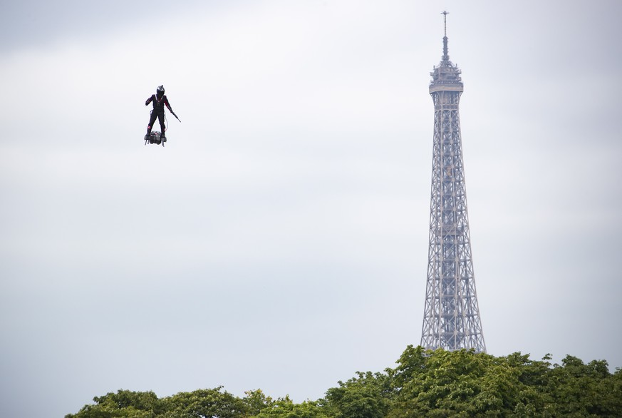 epa07716014 Professional pilot Franky Zapata demonstrates a flight on a 'flyboard', which the French army is considering using for military purposes, during the annual Bastille Day military parade on the Champs Elysees avenue in Paris, France, 14 July 2019. Bastille Day, the French National Day, is held annually on 14 July to commemorate the storming of the Bastille fortress in 1789.  EPA/IAN LANGSDON