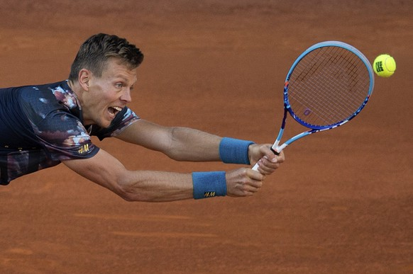 Tomas Berdych of the Czech Republic returns a shot to John Isner of the U.S. during the Madrid Open Tennis tournament in Madrid, Spain, Friday, May 8, 2015. (AP Photo/Paul White)